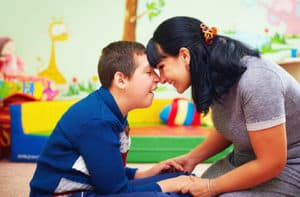 Boy with intellectual disability playing with carer