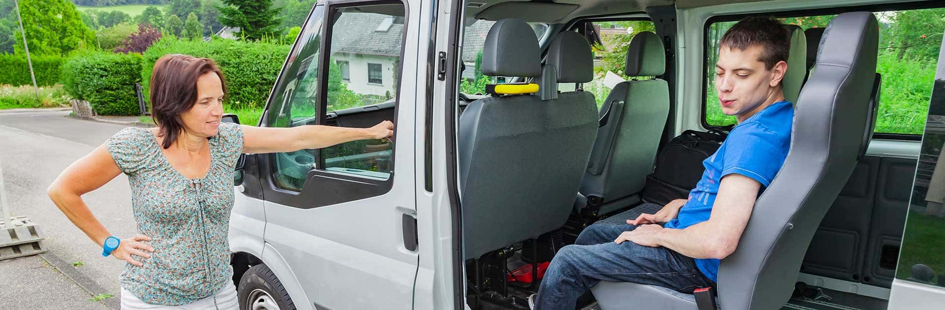 Disabled teenager sitting in van