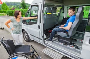 Man getting helped out of van into a wheelchair