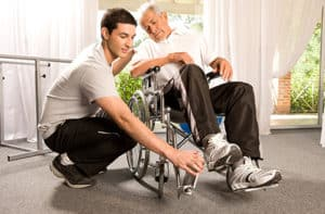 older man in wheelchair being helped by his carer