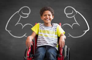 young boy in wheelchair with muscle arms drawn on blackboard behind him