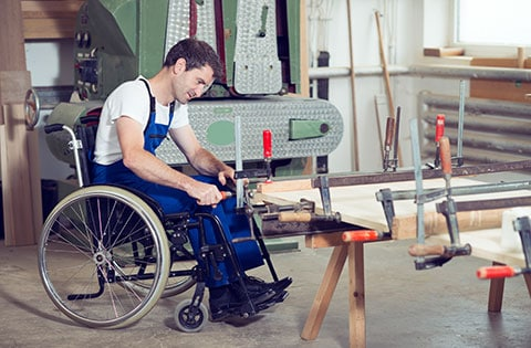 man in wheelchair working in a factory