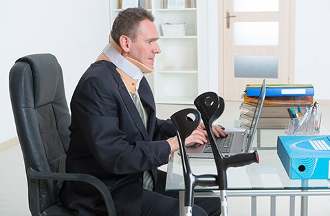 man with neck brace working at computer