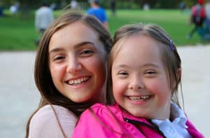 young girl with intellectual disability smiling at camera with girl friend
