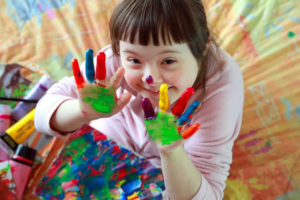 Downsyndrome girl smiling with painted hands