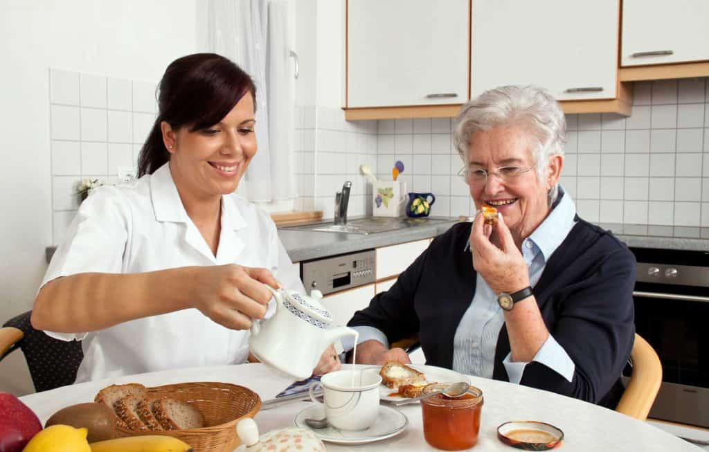 Nurse pouring tea for elderly lady