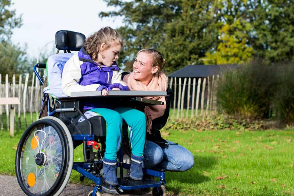 young girl in wheelchair with carer in a park